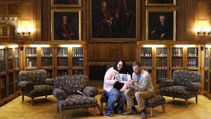 Lilly Ross (izq) le muestra fotos de familia a Andy Sandness, el hombre al que le transplantaron el rostro de su marido, cuando ambos se encontraron por primera vez en la biblioteca de la Clínica Mayo de Minnesota el 27 de octubre del 2017.