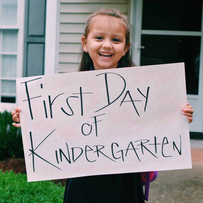 Niña sonriendo con cartel en el primer día de clases