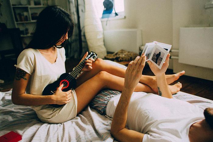 Mujer sentada en una cama tocando la guitarra mientras el hombre ve un álbum de fotos