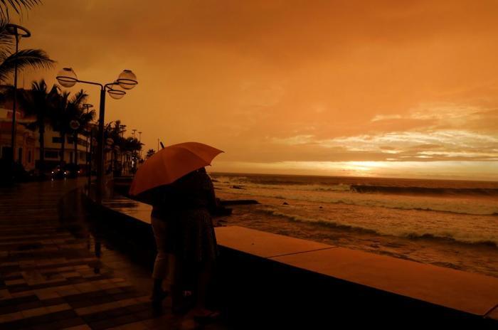 Residentes de Mazatlán en el paseo marítimo de la ciudad mientras el huracán Willa se acerca este martes.
