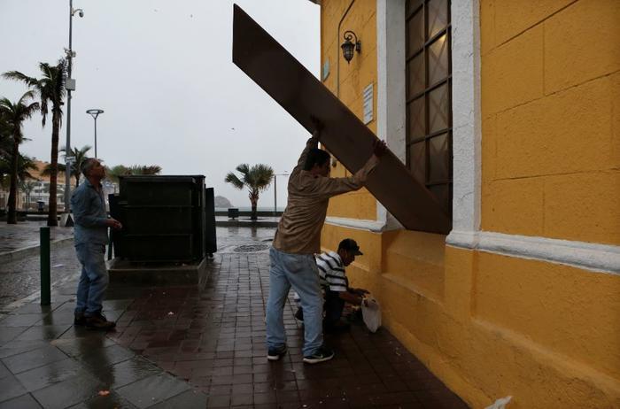 Ante la llegada del huracán Willa, residentes cubren este martes las ventanas de edificios en Mazatlán, México.