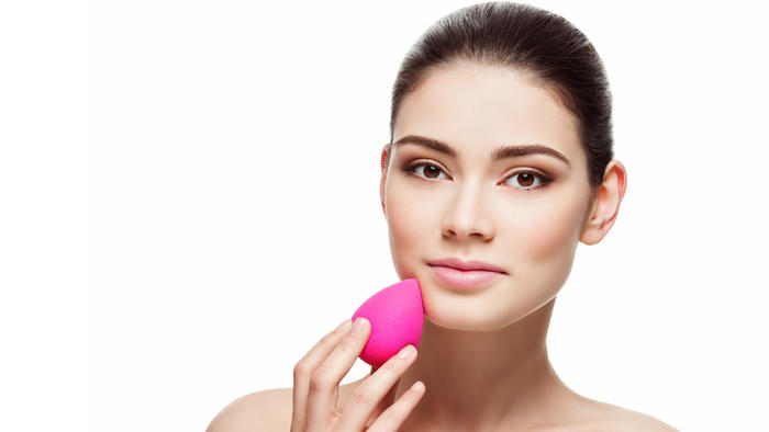 Mujer aplicandose maquillaje con beauty blender