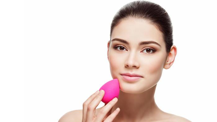 Mujer aplicandose maquillaje con beauty blender