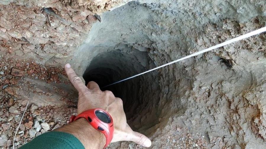 Un guardia civil señala el orificio, de apenas 30 centímetros de ancho, del pozo de más de 100 metros de profundidad por el que cayó un niño de dos años en una finca privada de la localidad malagueña de Totalán.