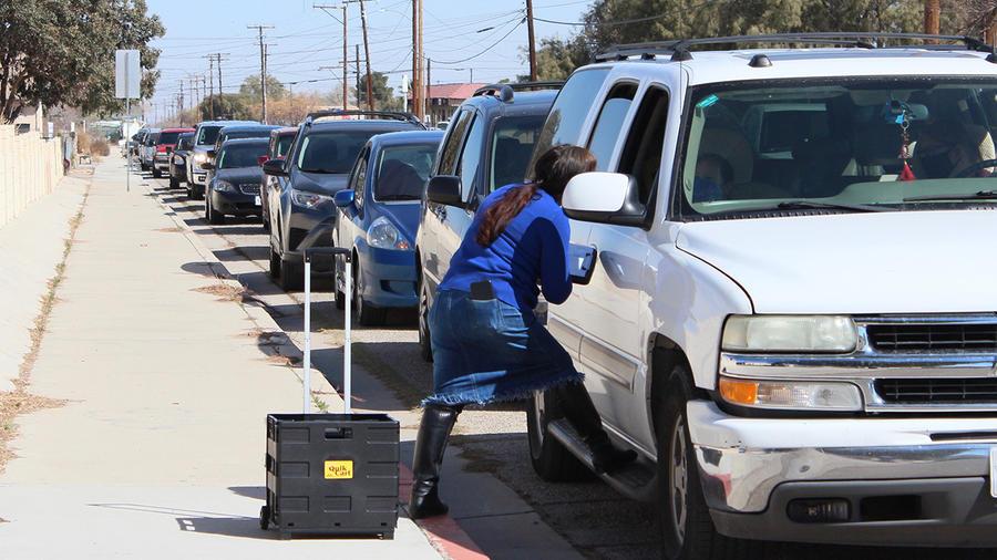 Leonor García, trabajadora de El Sol Neighborhood Educational Center, habla con conductores que esperan para recibir comida de un banco de alimentos en Adelanto, California, el 17 de marzo de 2021.