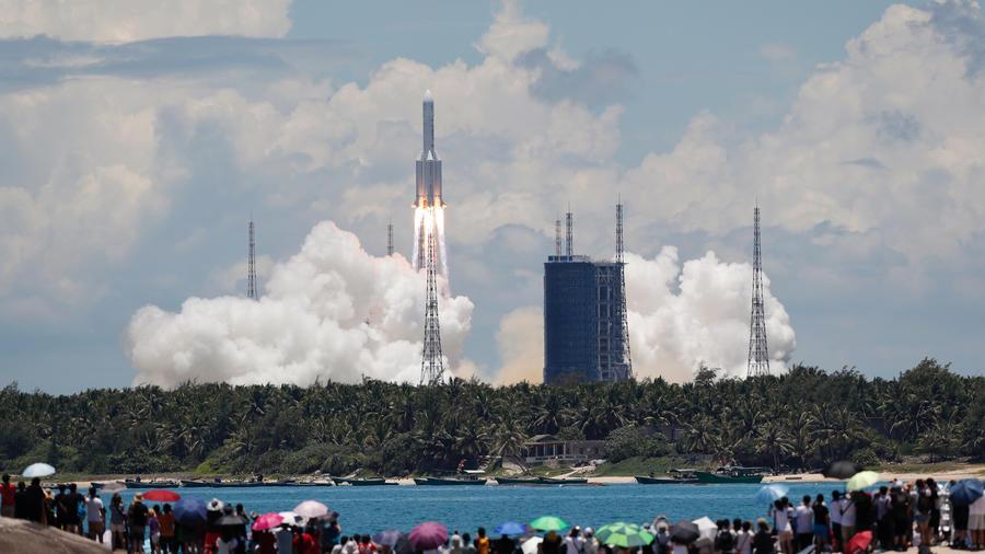 Expectadores observan desde una playa cómo el cohete Long March 5 Y-4 despega del Centro de Lanzamiento Espacial Wenchang en Wenchang, China, el 23 de julio de 2020.