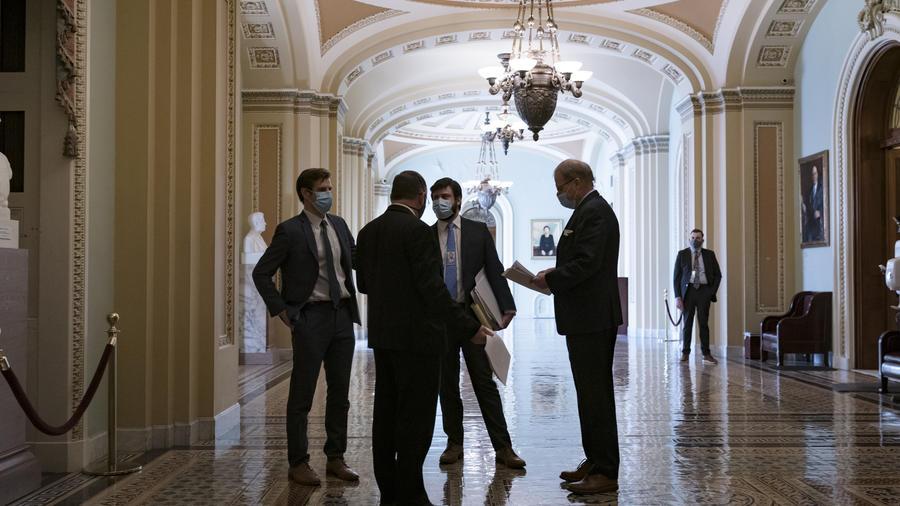 Empleados del Congreso esperan fuera de la cámara del Senado este viernes 5 de marzo de 2021, mientras continuaba este viernes la negociación para el plan de alivio económico por el COVID-19.