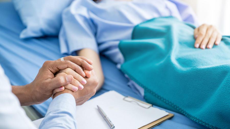 Doctor sosteniendo la mano de su paciente
