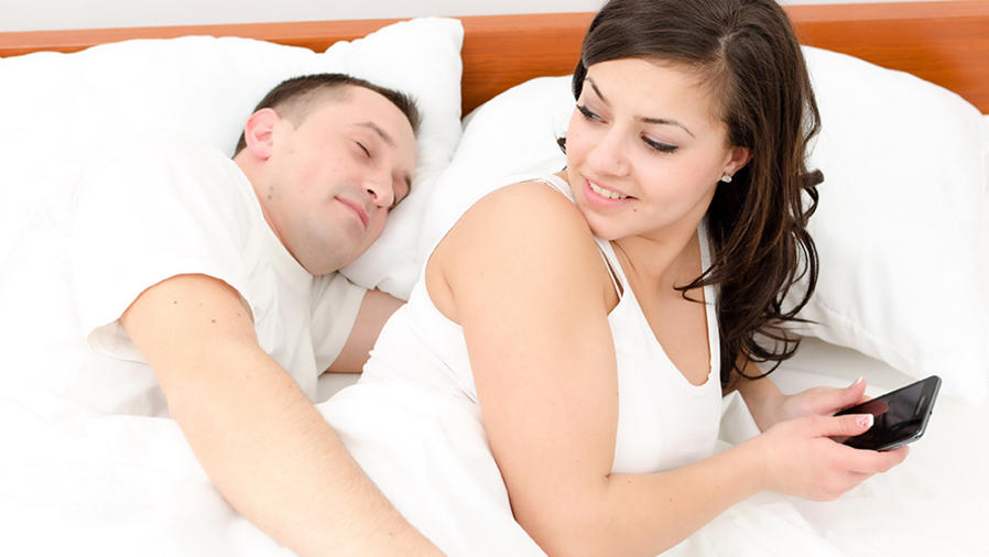 Pareja acostada en la cama viendo el celular y abrazada