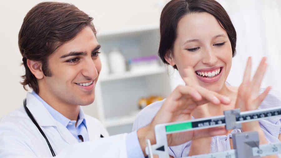 Mujer feliz en la báscula y su doctor