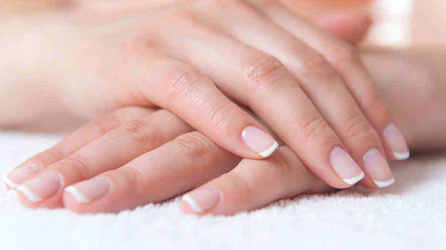 Mano de mujer con uñas naturales y sin esmalte