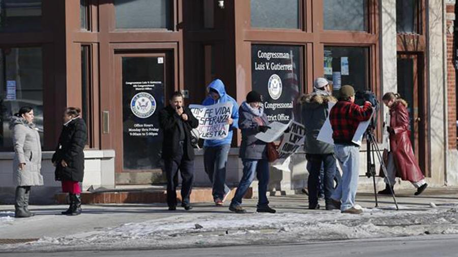 El padre José Landaverde (3 izda) encabezó hoy una protesta frente a la oficina del congresista demócrata Luís Gutiérrez en Chicago, para exigir que se ponga fin a las redadas y deportaciones del gobierno del presidente Barack Obama.