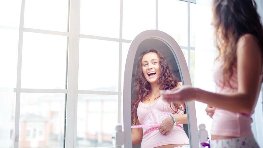 Mujer midiendo su cintura frente al espejo