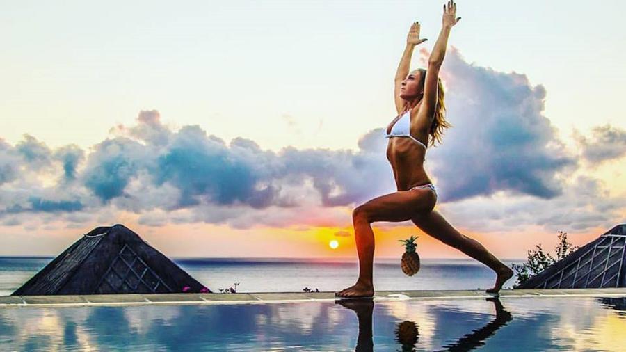 Kim Anami con bikini blanco levantando una piña