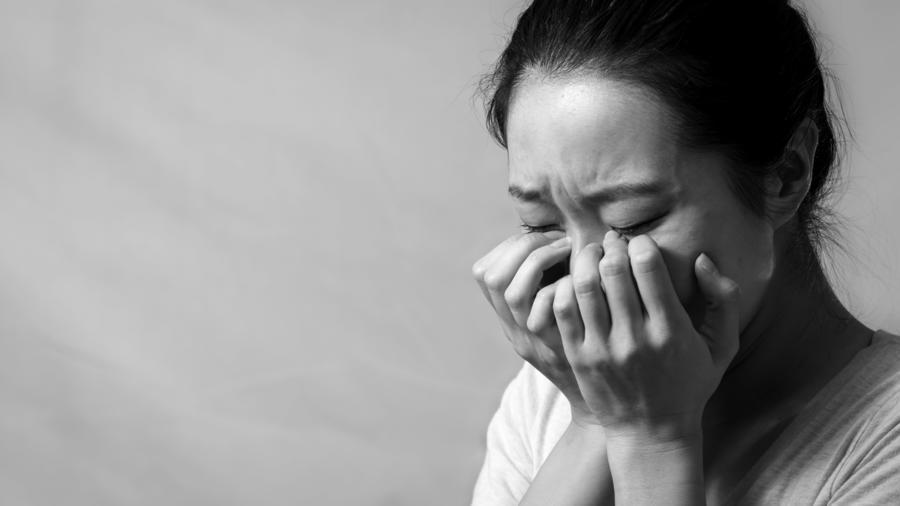 Mujer asiática con las manos en el rostro llorando