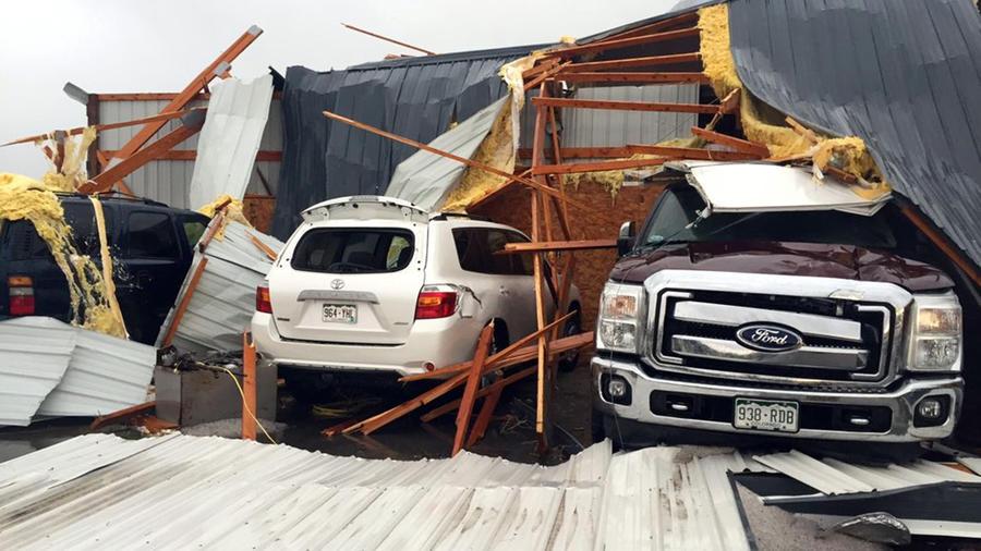 En la imagen, escombros sobre varios autos vehículos dañados por el paso de un tornado en el condado de Weld, en Colorado, el sábado 7 de mayo de 2016