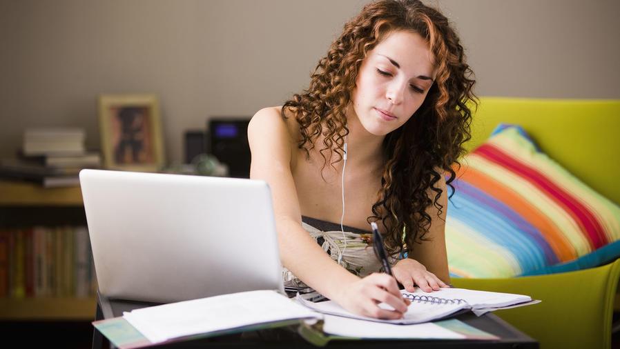 Joven estudiando en el living