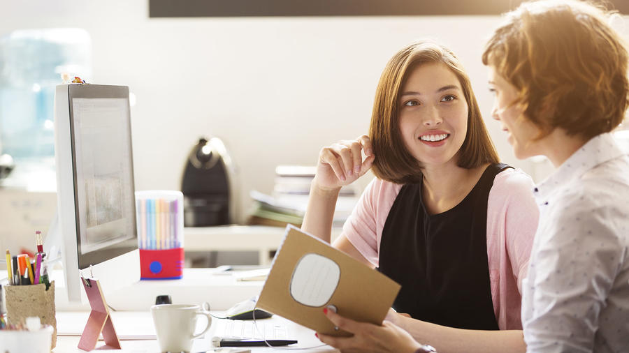Dos mujeres conversando en la oficina