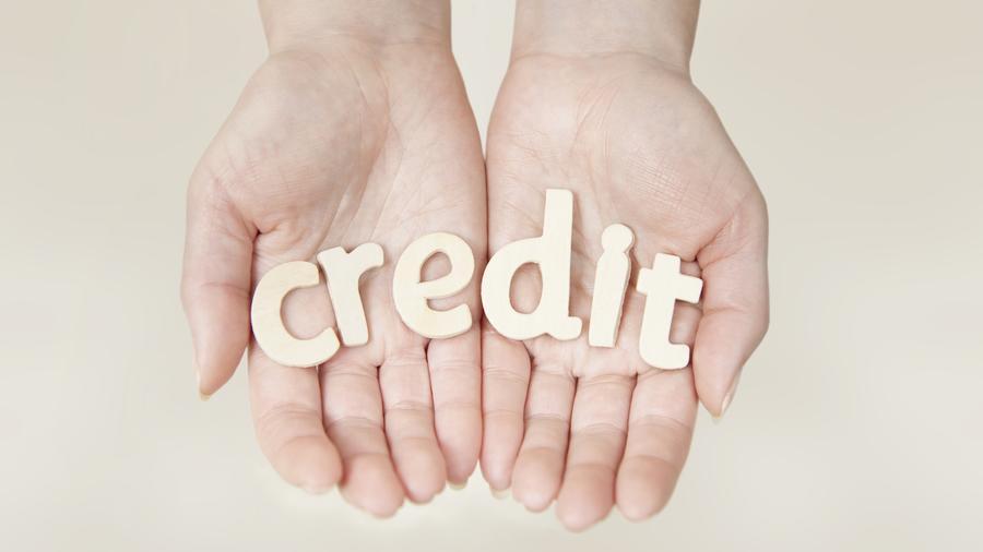 """Manos sosteniendo la palabra """"credit"""""""
