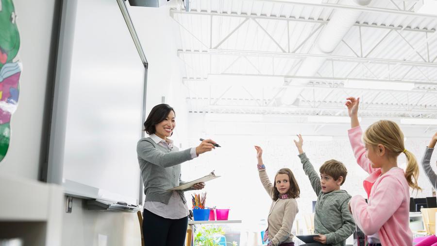 Alumnos en clase alzan la mano