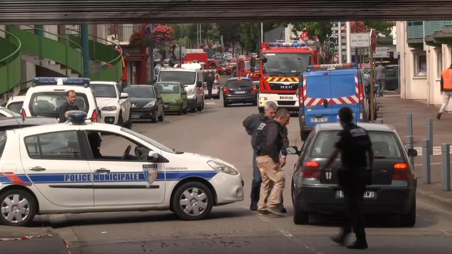 En esta imagen tomada de un video, policías hablan con un conductor tras cortar una calle durante una crisis de rehenes en Normandía, Francia, el 26 de julio de 2016. (BFM via AP)
