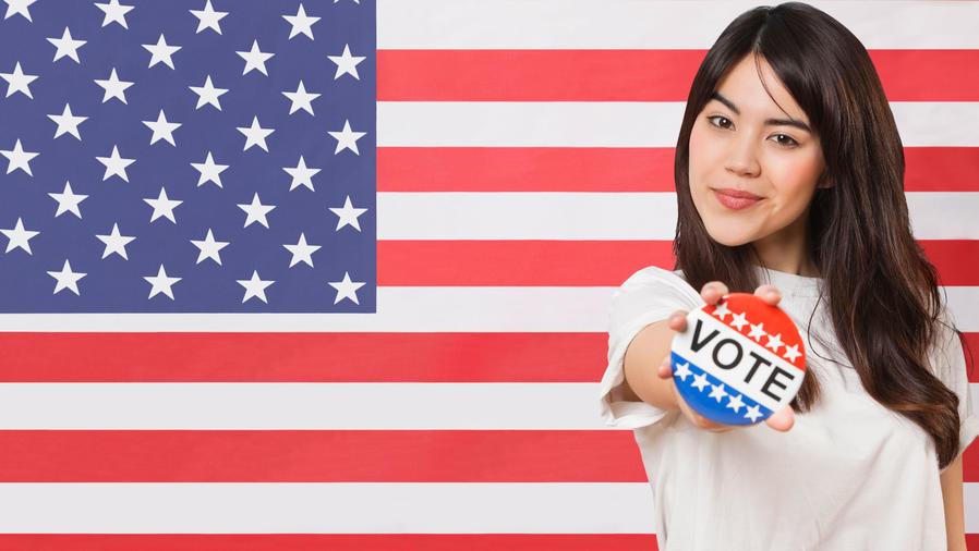 Mujer joven con cartel de Vote, frente a bandera de EEUU