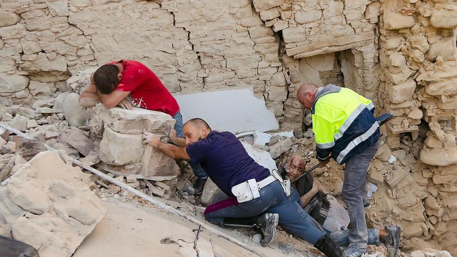 Un hombre llora mientras su amigo, a la derecha, que fue golpeado por escombros es ayudado por rescatistas en Amatrice, en el centro de Italia