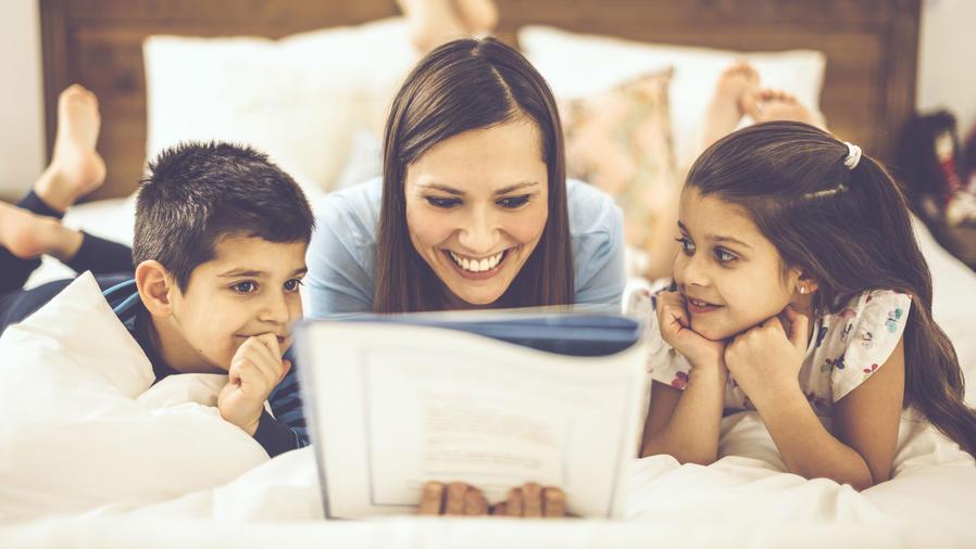Madre leyendo en la cama a sus dos hijos