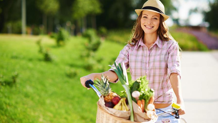 Mujer joven en bicicleta con frutas y verduras