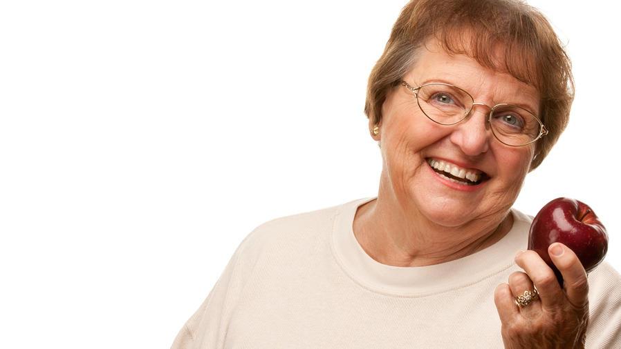 Abuela sonríe y sostiene manzana