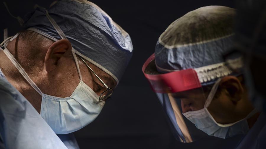 En esta imagen del 7 de octubre de 2016, el cirujano de oncología doctor Reynold López, a la izquierda, trabaja mano a mano con el médico residente Edgardo Cintron durante una operación de tiroides en el hospital de oncología Dr. Isaac González, en San Ju
