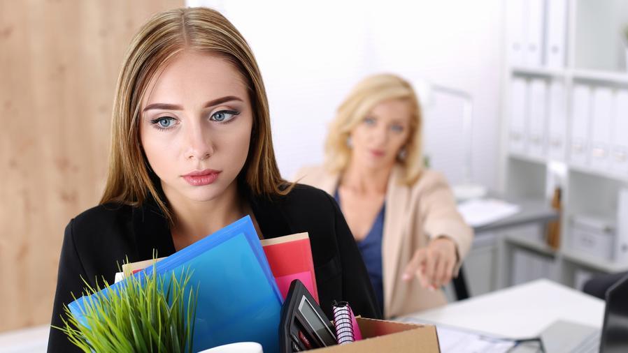 Mujer despedida con una caja con pertenencias