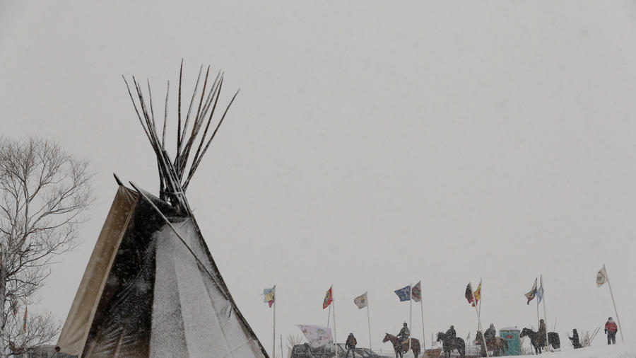 Young Native American men ride horses down a road lined with flags inside of the Oceti Sakowin camp during a snow fall, near Cannon Ball, North Dakota