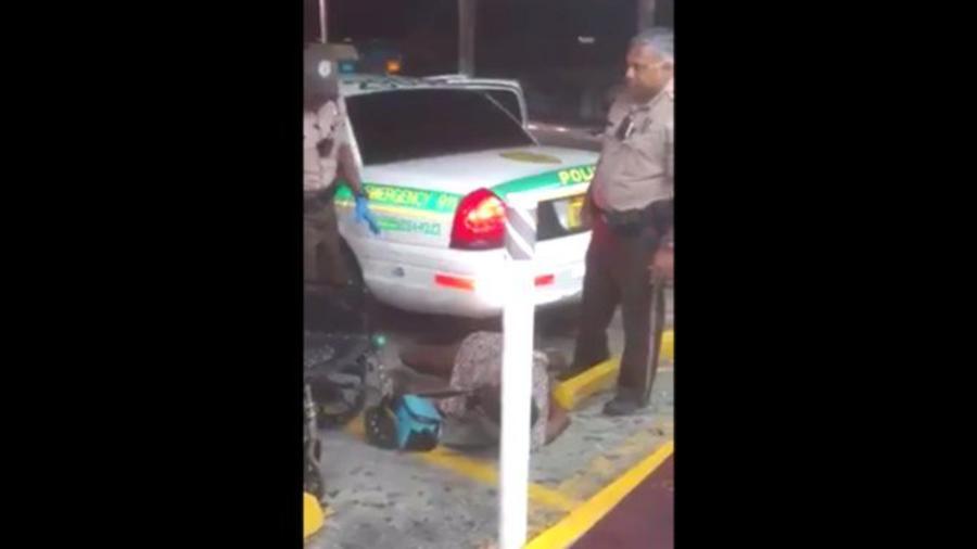 Mary Brown cae al piso rodeada de dos policías de Miami