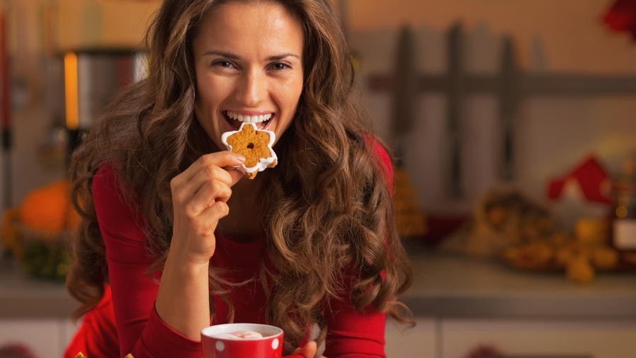 Mujer joven come galleta navideña