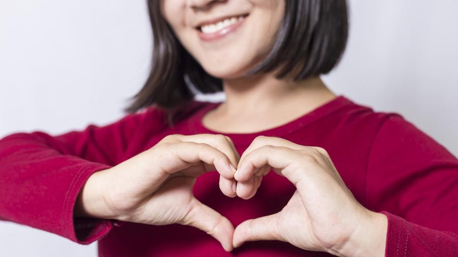 Mujer haciendo gesto de corazón con sus manos