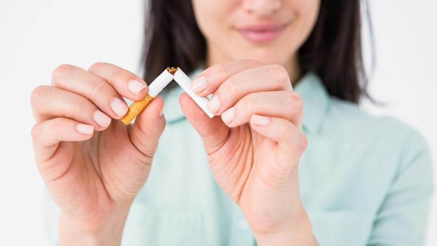 Mujer sonriendo mientras rompe un cigarrillo