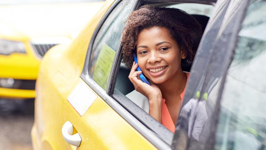 Mujer afroamericana hablando por smartphone en un taxi