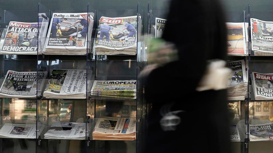 Un hombre pasa frente  a periódicos con titulares sobre el ataque terrorista cerca del Parlamento en Londres