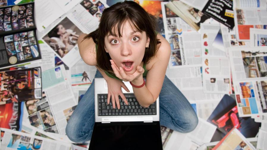 Chica sorprendida entre periódicos y revistas