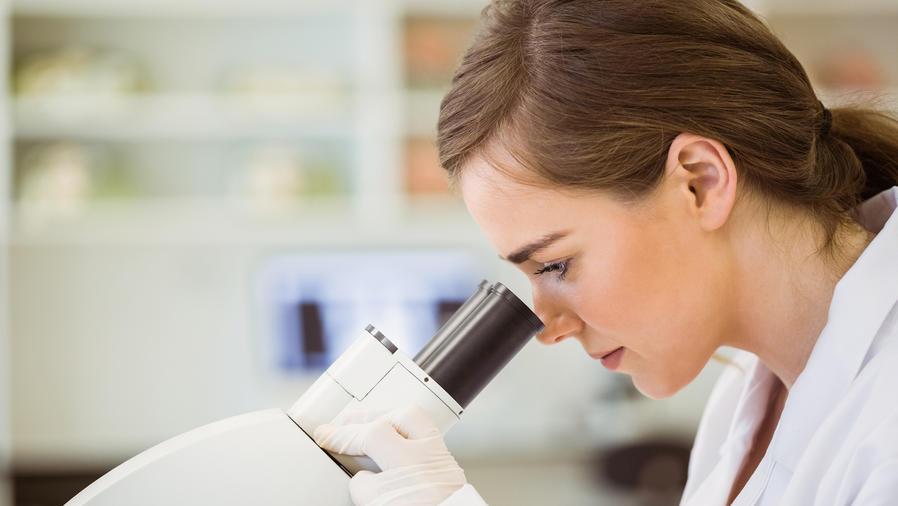 Científica mira a través del microscopio