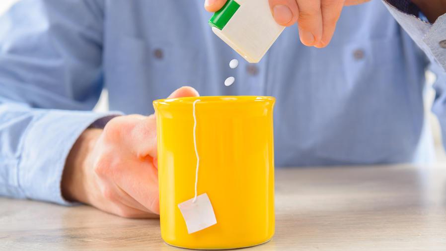 Hombre en camisa poniendo edulcorante en el té
