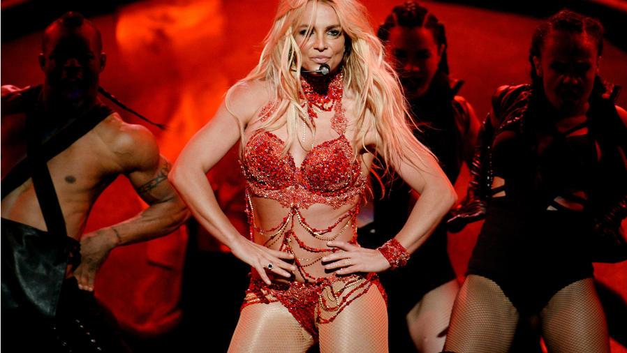 Britney Spears cantando en un bodysuit rojo