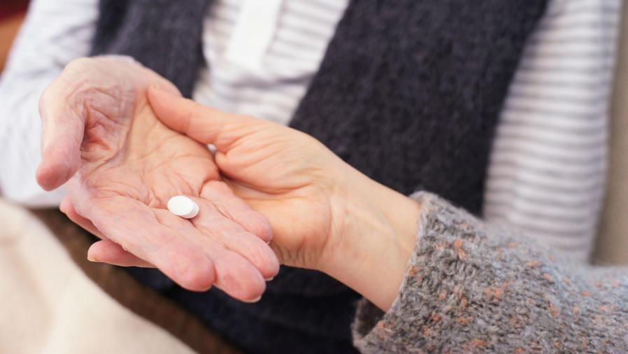 Hombre sosteniendo una aspirina en su mano
