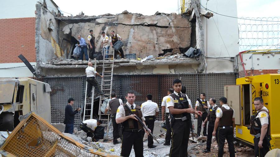 Guardias y policías inspeccionan una bóveda que los asaltantes explotaron temprano en Ciudad del Este, Paraguay, el lunes, 24 de abril de 2017.