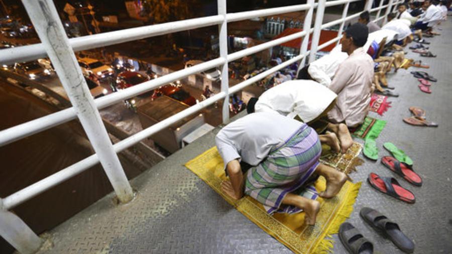 """Musulmanes realizan una oración de la tarde llamada """"tarawih"""" que marca la primera víspera del mes sagrado del mes de ayuno de Ramadán en un puente peatonal en Yakarta, Indonesia."""