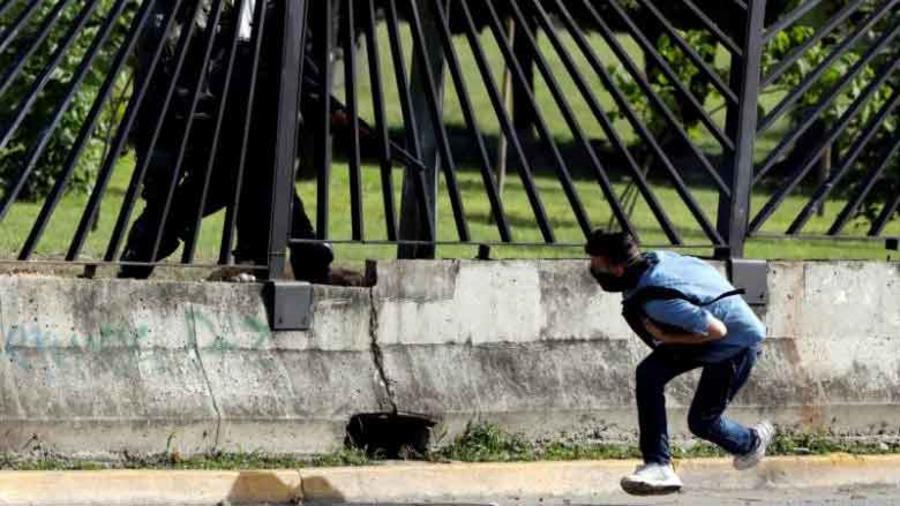 Manifestante en Venezuela mientra un agente le apunta con un rifle