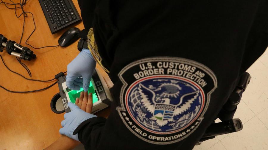 Agente de ICE toma huellas en McAllen, Texas