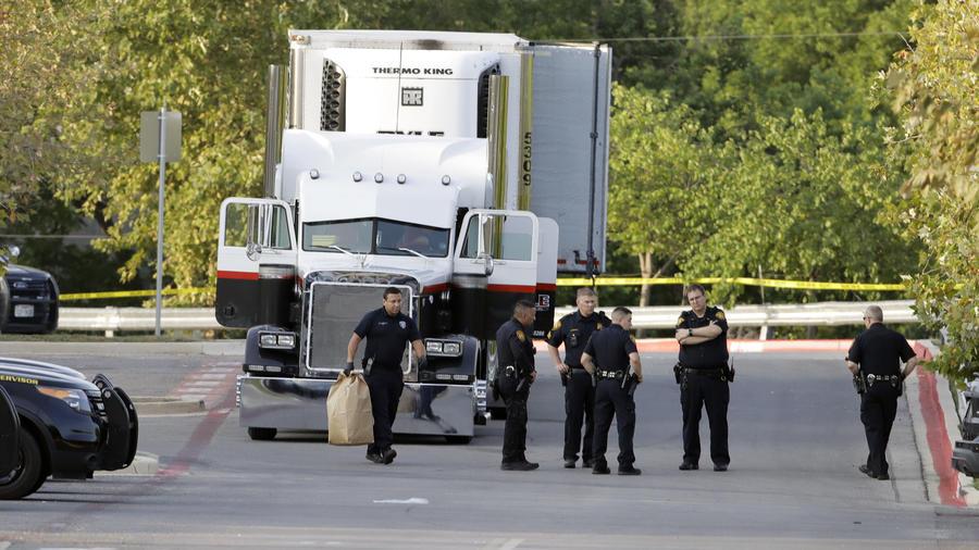Varios policías junto al remolque donde fueron halladas ocho personas muertas y al menos 30 sobrevivientes en el estacionamiento de una tienda Walmart en San Antonio, el domingo 23 de julio de 2017.