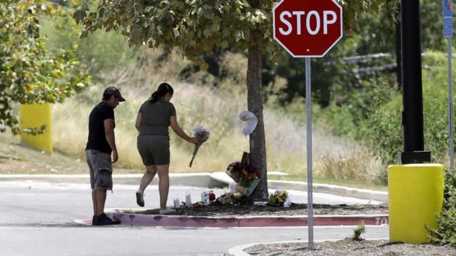 Dos personas dejan ramos de flores en el lugar donde encontraron el trailer con indocumentados en Texas